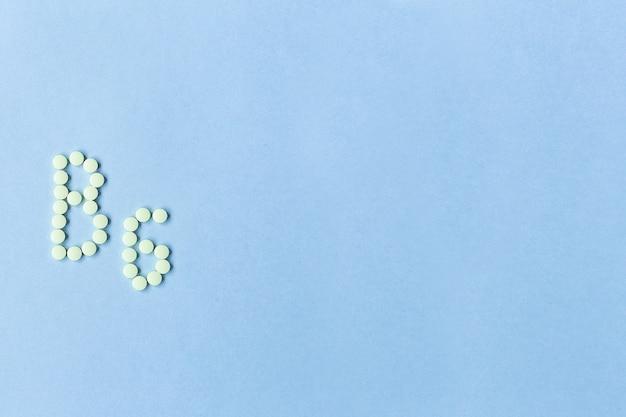청록색 배경 위에 단어 b6을 형성하는 비타민 b6 알약