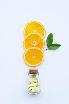 Vitamin c bottle and pills with orange fruit on white.