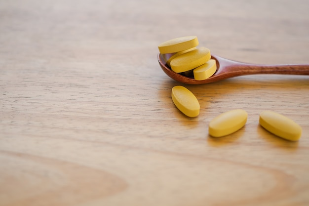 木のテーブルが付いている木のスプーンの上のビタミンc