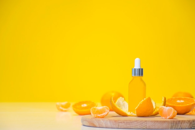 コピースペースと黄色の背景にオレンジ色の部分とみかんの皮のビタミンc血清化粧品ボトル。