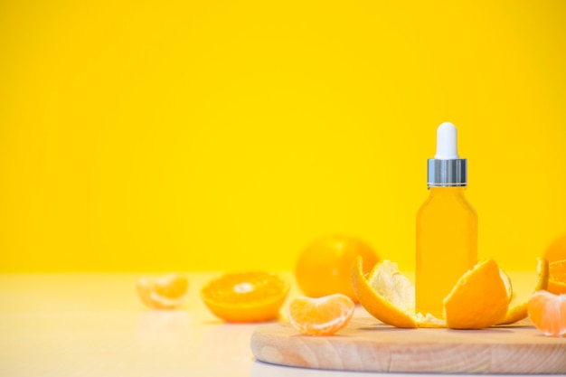 Vitamin c serum cosmetic bottle in tangerine peel with orange pieces on yellow background with copy space.