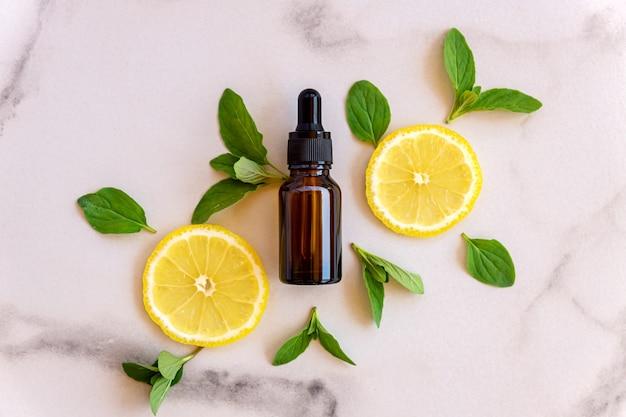 Сыворотка с витамином с в косметической бутылке с дольками лимона и цитрусовых с зелеными листьями на белой поверхности