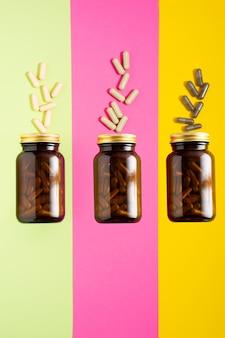 トレンディな影の概念と黄色、ピンク、緑の背景にガラス瓶のビタミンカプセルの丸薬