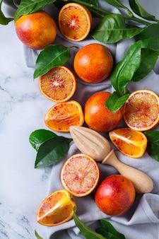 Витамин, чистое питание, веганская концепция здорового питания. целые и нарезанные сладкие сицилийские апельсины на белом мраморном столе. плоский фон вид сверху