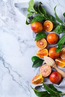 Витамин, чистое питание, веганская концепция здорового питания. целые и нарезанные сладкие сицилийские апельсины на белом мраморном столе. вид сверху плоская копия космического фона