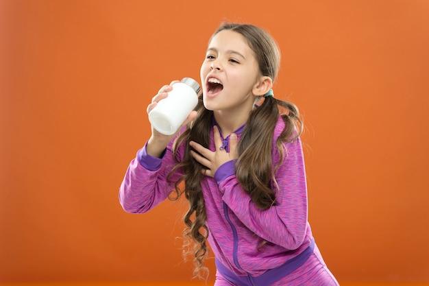 Концепция витамина. нужны витаминные добавки. милая девочка ребенка принимает лекарства. лечение и медицина. натуральный продукт. детские поливитамины. принимайте витаминные добавки. девушка держит бутылку с лекарствами.