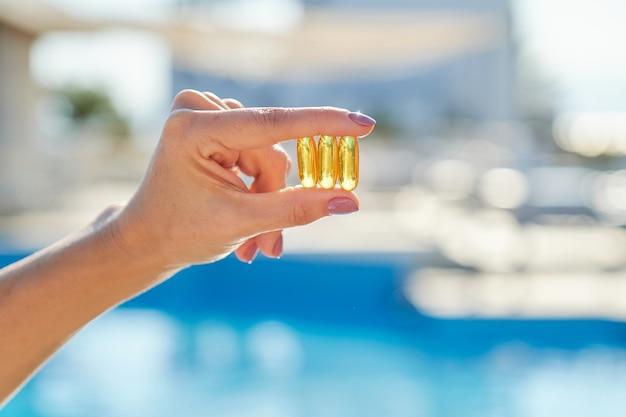 ビタミンd、e、a魚油カプセルタラ肝油オメガ3の女性の手、背景の太陽の青い水。健康的なライフスタイル、栄養、栄養補助食品、ダイエット