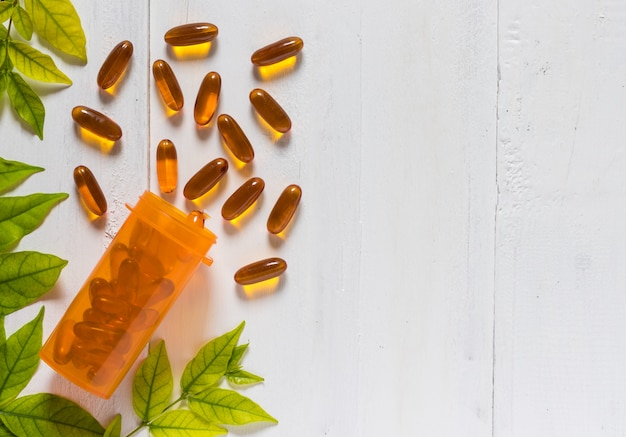 Vitamin d from fish oil capsules in an orange bottle on white wooden background