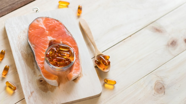 Vitamin d source from fish oil capsules and salmon on wooden background