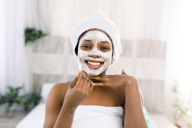 ビタミンフェイシャルマスク。スパでマスクの顔を持つアフリカの笑顔の女性