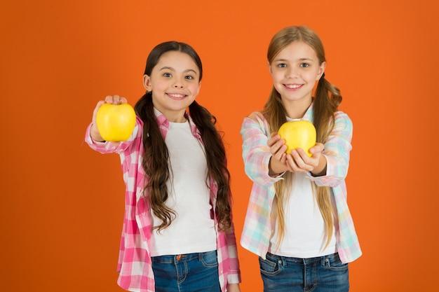 어린이를 위한 비타민 과일 영양. 건강한 생활. 학교에서 무료로 신선한 과일을 배포합니다. 여자 아이 캐주얼 스타일은 사과 과일 오렌지 배경을 먹습니다. 여학생들은 사과 과일을 먹습니다. 학교 급식.