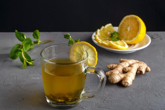 Витаминно-имбирный напиток с медом, мятой и лимоном в стеклянной чашке рядом с ингредиентами на бетонной стене.