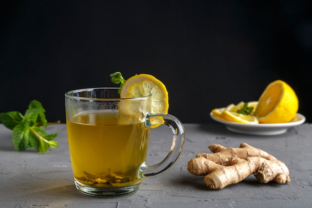 Vitamin ginger drink with honey mint and lemon in a glass cup near ginger root and lemon on a concrete background. horizontal photo