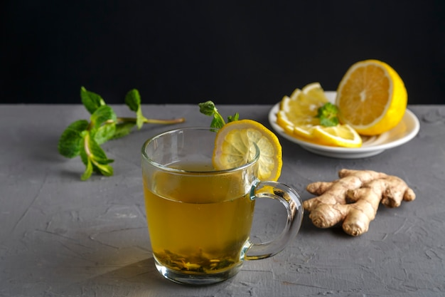 Vitamin ginger drink with honey mint and lemon in a glass cup near the ingredients on a concrete background