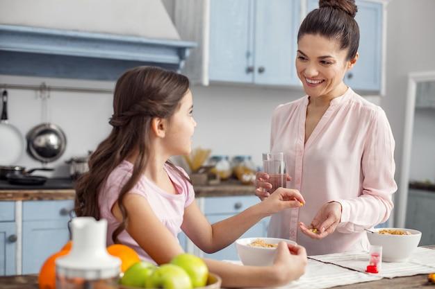ビタミン摂取量。笑顔で娘と朝食を食べてテーブルに座っている女の子にビタミンを与えている格好良い嬉しい黒髪の若い母親