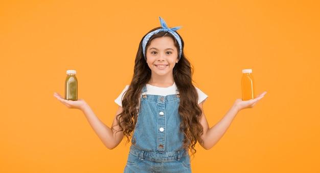 비타민 주스. 비타민 영양. 신선한 스무디. 오렌지 신선한 스무디를 마시는 소녀. 채식주의 개념입니다. 내 병에 딸기입니다. 과일 에너지. 웃는 아이가 스무디 병을 들고 있습니다. 건강한 음식.