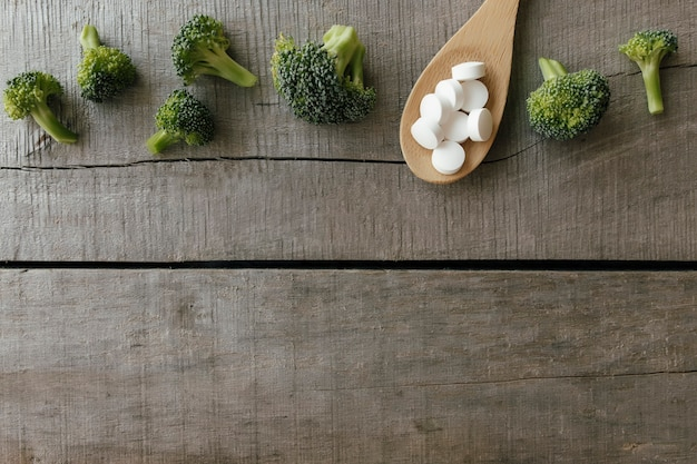 Vitamin or medicine capsules, broccoli on wooden spoon on wooden background. health therapy or treatment concept. vitamin pills.
