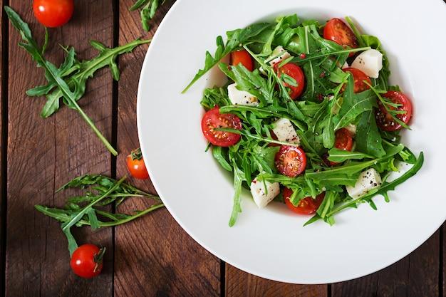 Витаминный салат из свежих помидоров, рукколы, сыра фета и перца. диетическое меню. правильное питание. вид сверху. квартира лежала.