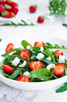 시금치 잎 치즈와 견과류를 곁들인 딸기의 비타민 샐러드 비건 음식 케토와 팔레오 다이어트