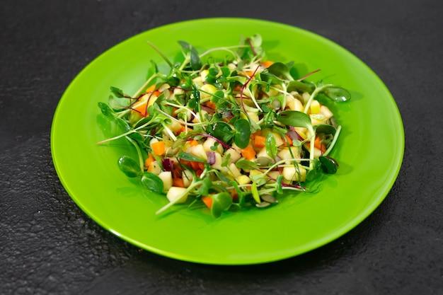 Витаминный салат на зеленой тарелке.