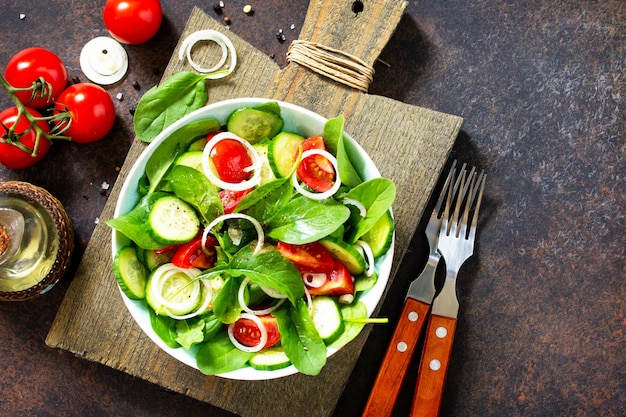 Vitamin snack salad with fresh vegetables and spinach on a dark stone table top view flat lay