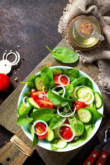 Vitamin snack salad with fresh vegetables and spinach top view flat lay background