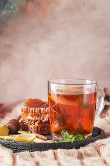 秋の背景を持つガラスカップのビタミンの健康的な海クロウメモドキ茶