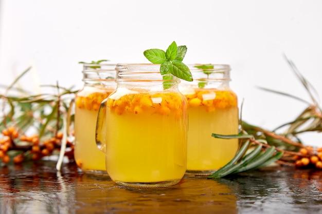 Витаминный здоровый облепиховый чай в маленьких стеклянных чашках со свежими сырыми облепиховыми ягодами, медом