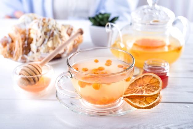 Витаминный здоровый облепиховый чай в маленьком стеклянном чайнике с ягодами облепихи и