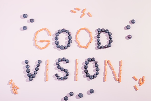 ピンクの背景の健康な目のためのビタミンとサプリメント。良い視力の概念を維持する方法。ブルーベリーとオレンジのカプセルは、良い視力、フラットレイ、トップビューの言葉を形成します