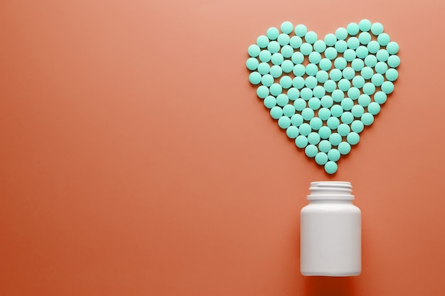 Vitamins b 12 on a red heart-shaped substrate, poured out of a white jar.
