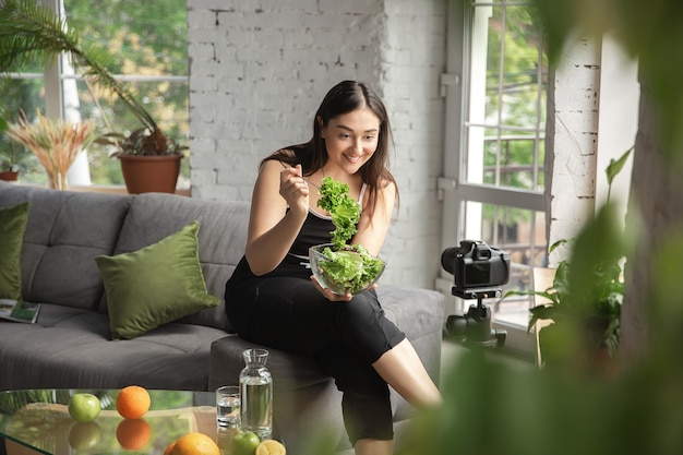 Vitamins. caucasian blogger, woman make vlog how to diet and lost weight, be body positive, healthy eating. using camera recording her green salad preparing. lifestyle influencer, wellness concept.