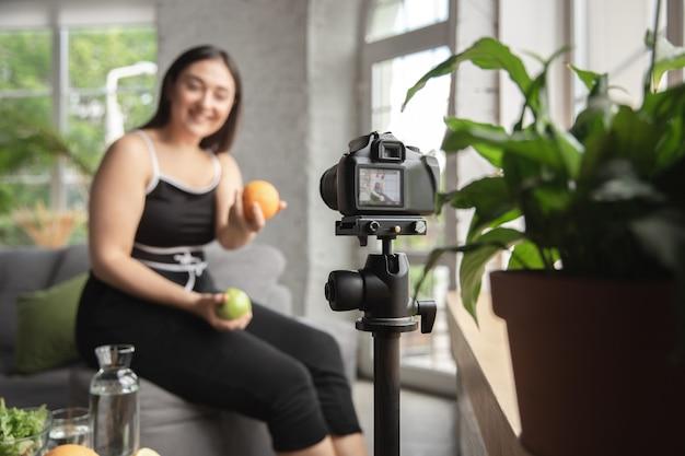 ビタミン。白人のブロガー、女性は、ダイエットと減量の方法をvlogで作成し、体をポジティブにし、健康的な食事をします。彼女のフルーツサラダの準備を記録するカメラを使用します。