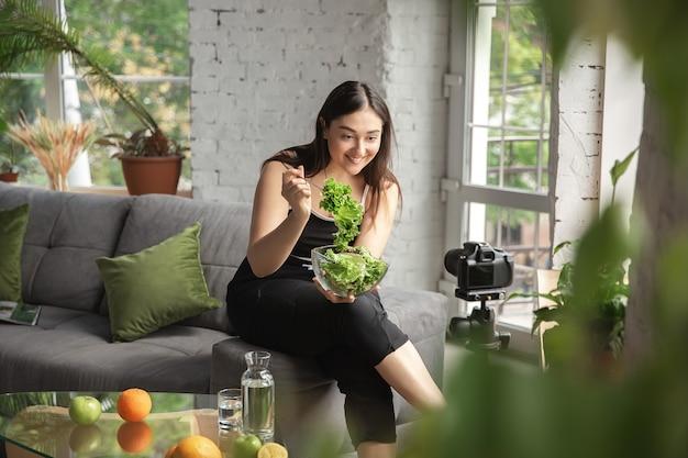 비타민. 백인 블로거, 여성은 다이어트와 체중 감량 방법을 vlog로 만들고 몸에 긍정적이고 건강한 식생활을 합니다. 카메라를 사용하여 그린 샐러드를 준비하고 있습니다. 라이프 스타일 인플루언서, 웰빙 개념.