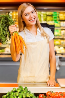 Vitamins for the customers. cheerful young female seller smiling at camera and holding carrots while standing at a food store
