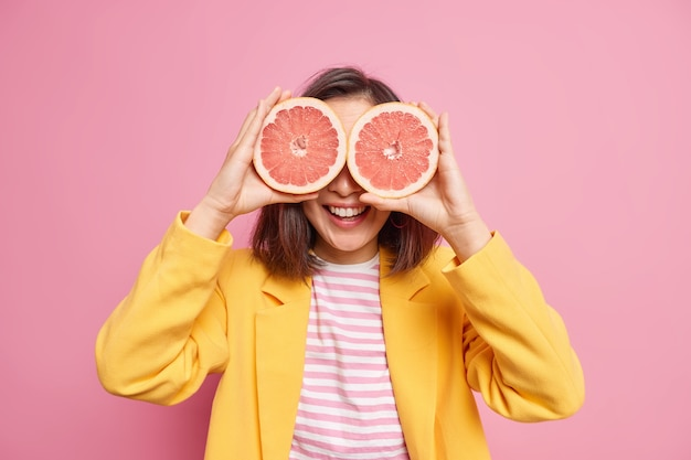 Витамины для ухода за кожей и красоты. позитивная темноволосая молодая женщина прикрывает глаза половинками грейпфрута, одетыми в модную одежду, изолированными над розовой стеной, имеет летнее настроение. цитрусовый фрукт