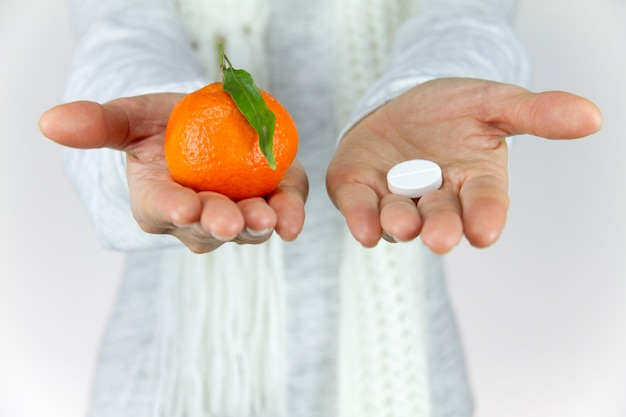 Vitamins from fruit or drugs? a sick young woman with a scarf on her neck shows a mandarin in her right hand and an aspirin on her left
