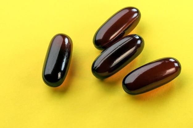 茶色のゼラチンカプセル濃縮オメガ3魚油ブレンドのクローズアップマクロ写真のビタミン