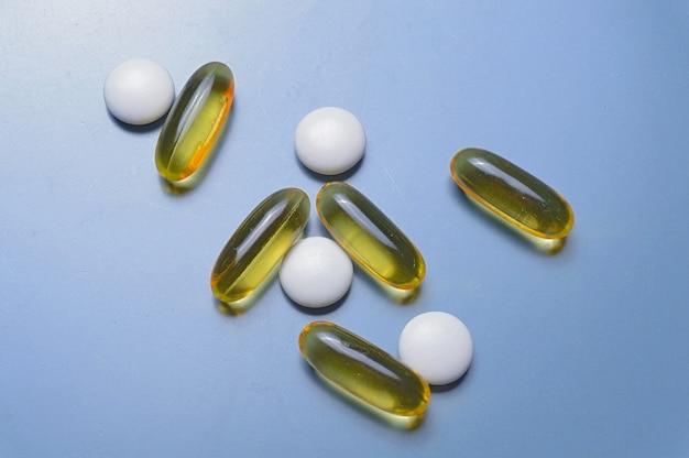 Витамины в капсулах и таблетках на серой поверхности