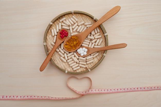 編組竹皿の中にある木のスプーンに含まれるビタミン、ミネラル、栄養補助食品