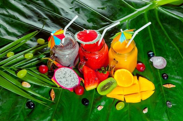 トロピカルグリーンリーフの上に立っているスイカ、マンゴー、ドラゴンフルーツのビタミンスムージー。夏休みと新鮮なお食事