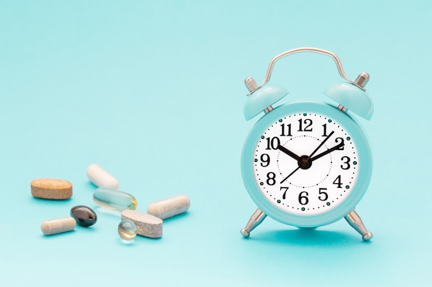Vitamins, supplements and alarm clock on pastel blue background.
