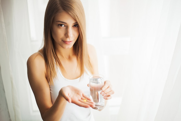 Vitamins and supplements. woman taking a tablet. close up hand with a pill and the mouth.