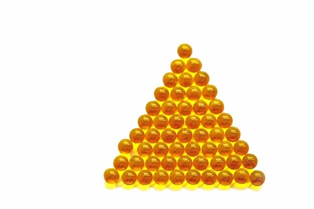 白い背景の上のピラミッドに積み重ねられたビタミン透明な黄色のボール。