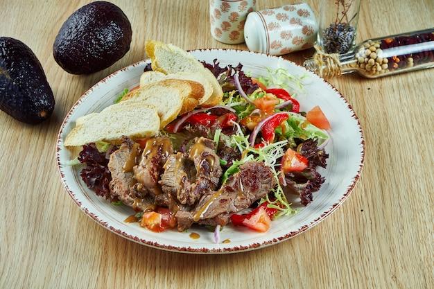 Сочный мясной салат с запеченной телятиной vitello tonato, листьями салата, луком и помидорами черри в белой миске на деревянном столе. здоровая пища. крупным планом вид