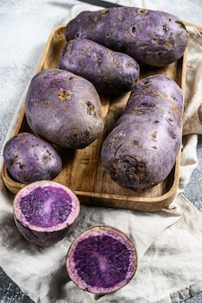 Vitelotte raw potato on a chopping board. top view