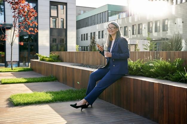 사무실 밖에서 커피를 마시며 세련된 정장을 입은 활기찬 회색 머리 여성