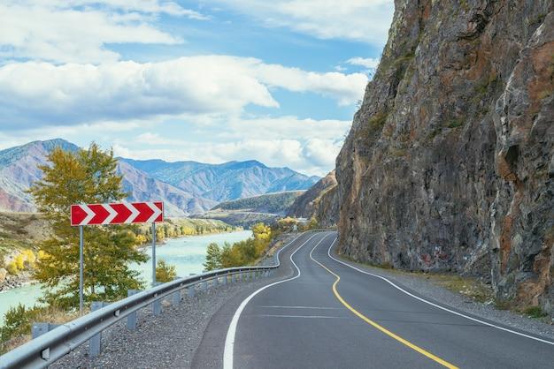 日差しの中で大きな山川に沿って山の高速道路と鮮やかな秋の風景。秋の色の広いターコイズブルーの川と山道の明るい高山の風景。秋の山の高速道路