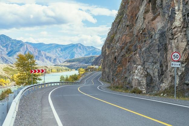 日差しの中で大きな山川に沿って山の高速道路と鮮やかな秋の風景。紅葉の広いターコイズブルーの川と山道の明るい高山の風景。秋の山の高速道路