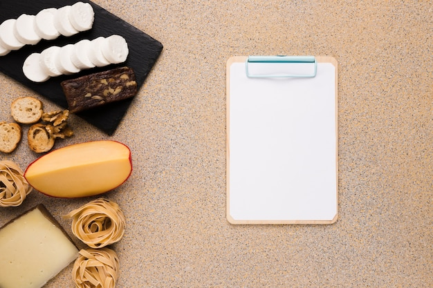 Vivid cheese slices ; bread slice; walnut and pasta balls near blank paper on clipboard over plain background